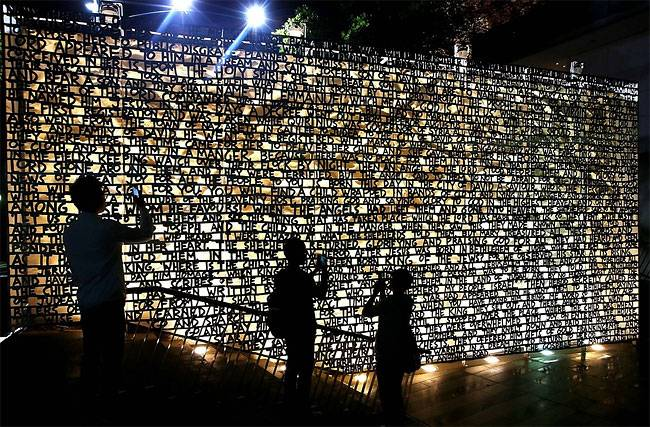 Туристы фотографируют  стену, которая объясняет историю Рождества Иисуса на площади в Мельбурне, Австралия