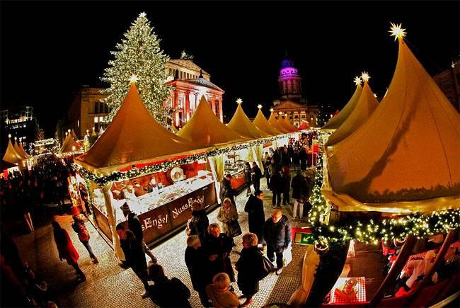 Люди посещают Рождественский рынок на Gendarmenmarkt Square в Берлине