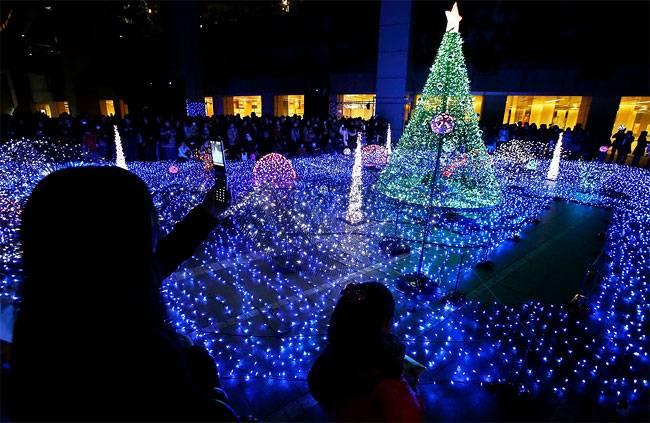 Люди собираются, чтобы посмотреть  включение рождественских огней в Токио.